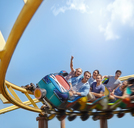 Cheering friends riding roller coaster at amusement park - CAIF11324