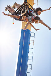 Friends bungee jumping at amusement park - CAIF11330