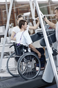 Physical therapists guiding man in wheelchair on treadmill - CAIF11348
