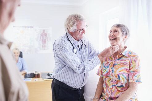 Doctor checking senior woman's glands at checkup - CAIF11396