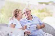 Senior couple hugging and drinking coffee on patio - CAIF11414