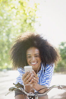 Smiling woman with afro listening to music with headphones and mp3 player on bicycle - CAIF11426