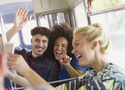 Enthusiastic friends taking selfie on bus - CAIF11429