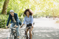 Friends riding bicycles in park - CAIF11441