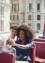 Couple taking selfie on double-decker bus - CAIF11444