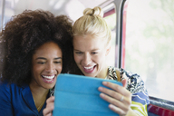Enthusiastic friends taking selfie with digital tablet on bus - CAIF11465