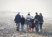 Multi-generation family walking in a row on beach - CAIF11486
