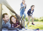 Smiling couple in tent watching kids running in grass - CAIF11489