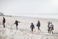 Multi-generation family walking on sunny beach - CAIF11498