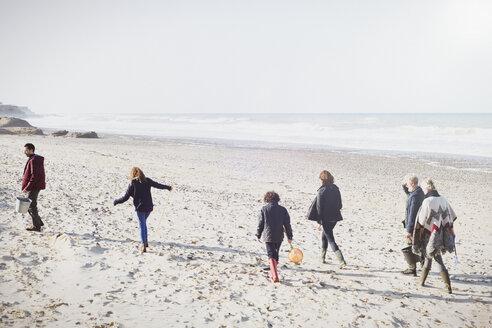Multi-generation family walking on sunny beach - CAIF11498