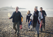 Multi-generation family walking on sunny beach - CAIF11501