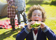 Enthusiastic boy taking large bite of hamburger at sunny campsite - CAIF11513
