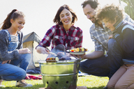 Family barbecuing at campsite grill - CAIF11519