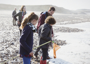 Multi-generation family clamming on rocky beach - CAIF11522