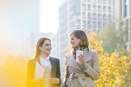 Businesswomen walking with coffee in city - CAIF11555