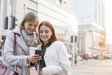 Smiling businesswomen texting and drinking coffee on city street - CAIF11558