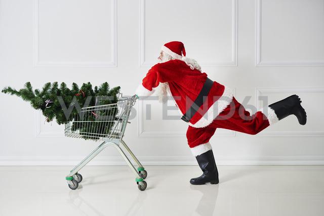 Santa Claus transporting Christmas tree in a shopping cart - ABIF00106