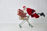 Santa Claus carrying Christmas presents with shopping cart - ABIF00109