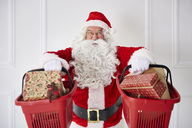Portrait of happy Santa Claus holding two shopping baskets with Christmas presents - ABIF00112