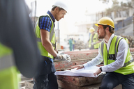 Construction worker and engineer reviewing blueprints at construction site - CAIF11593