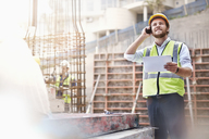 Engineer with digital tablet talking on cell phone at construction site - CAIF11596