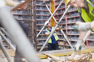 Construction worker examining structure at construction site - CAIF11599