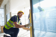 Construction worker using level tool on window at construction site - CAIF11602