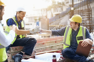 Construction workers and engineer enjoying coffee break at construction site - CAIF11605
