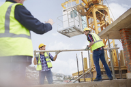 Construction workers lifting metal pole below crane at construction site - CAIF11608