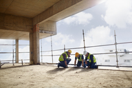 Construction workers working at highrise construction site - CAIF11611