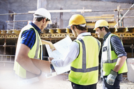 Construction workers and engineer reviewing blueprints at construction site - CAIF11614