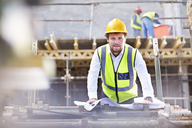 Portrait confident engineer with blueprints at construction site - CAIF11620
