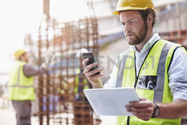 Construction worker with digital tablet texting with cell phone at construction site - CAIF11623