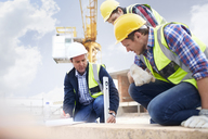Construction workers and engineer using level tool at construction site - CAIF11629