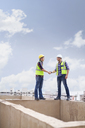 Construction workers handshaking at highrise construction site - CAIF11632