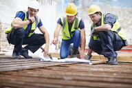Construction workers and engineer reviewing blueprints at construction site - CAIF11635