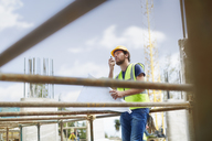 Engineer with blueprints using walkie-talkie at construction site - CAIF11638