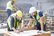 Construction worker and engineer revising blueprints at construction site - CAIF11641