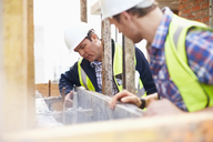 Construction workers examining structure at construction site - CAIF11644