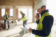 Foreman with digital tablet using walkie-talkie at construction site - CAIF11653