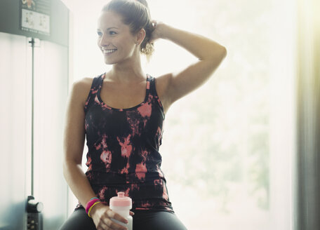 Smiling woman with water bottle resting at gym - CAIF11689