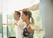 Smiling woman with arms outstretched in aerobics class - CAIF11728