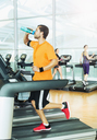 Man drinking water and running on treadmill at gym - CAIF11734