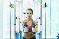 Focused woman using cable exercise equipment at gym - CAIF11749