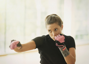 Woman with exercise gloves shadow boxing - CAIF11755