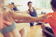 Fitness instructor with arms outstretched leading class in studio - CAIF11764