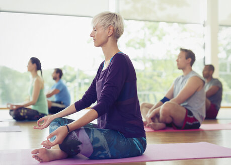 Serene woman in lotus position in yoga class - CAIF11767