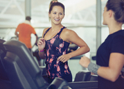 Smiling women talking on treadmills at gym - CAIF11770