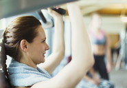 Close up woman using exercise equipment at gym - CAIF11773