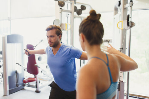 Female personal trainer guiding man doing cable chest fly at gym - CAIF11776